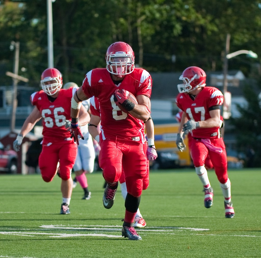 Montclair State University football player returns a punt for a touch down guarded by two players. 2012